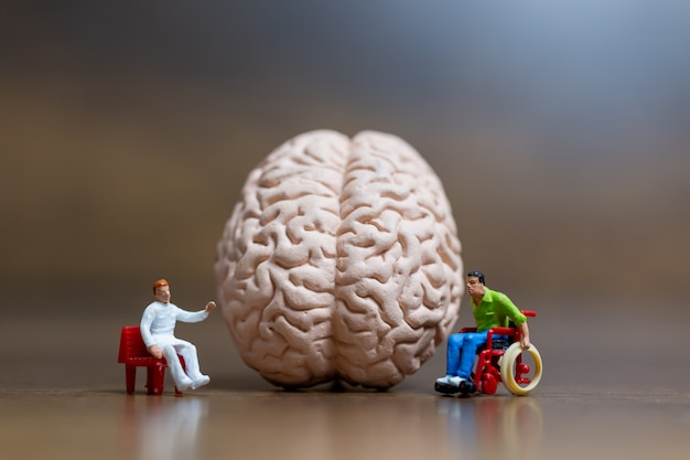 Миниатюрные люди, хирург поговорил с пациентом о травмах головного мозга. концепция медицинского здравоохранения и хирургического врача.