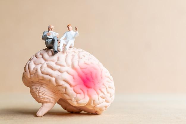 Миниатюрные человечки хирург рассказал пациенту о травмах головного мозга. концепция всемирного дня инсульта.