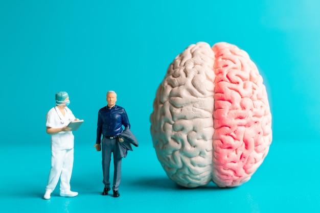 미니어처 사람 외과의사는 환자와 뇌 손상에 대해 이야기했습니다. 세계 뇌졸중의 날 개념입니다.