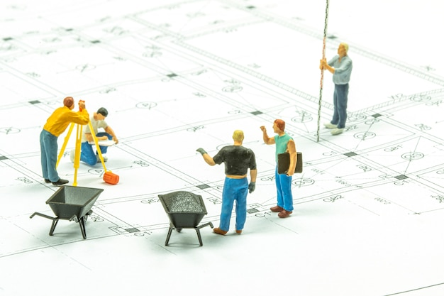 Miniature people surveyor technician is measuring the distance to build a house.