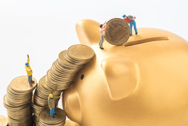 Miniature people team are trying to move coins from stack to gold piggy bank