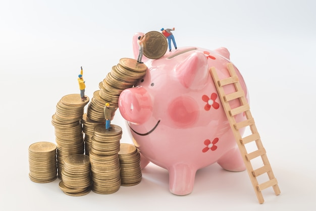 Miniature people team are trying to move coins from stack to piggy bank