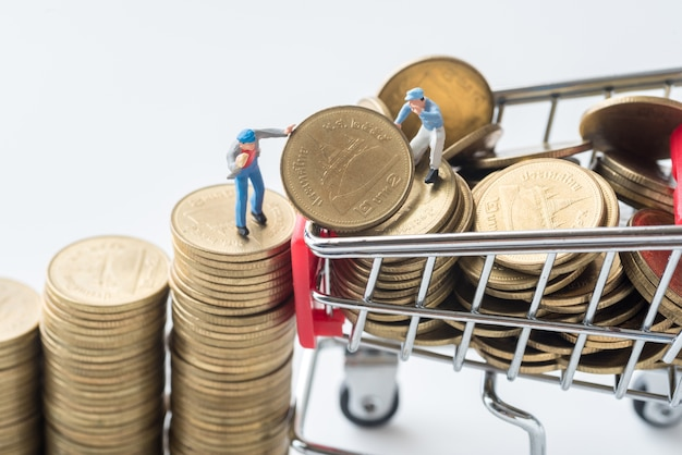 Miniature people team are trying to move coins from stack to shopping cart