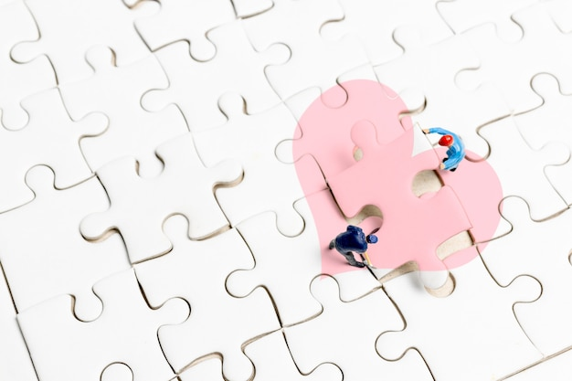 Miniature people the team is working on a puzzle piece with a heart shape,