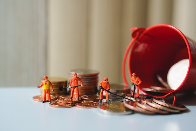 Miniature people, technician working on stack coins using as business and industry concept