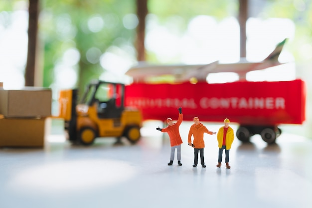 Miniature people, technicians team standing on transportation vehicle