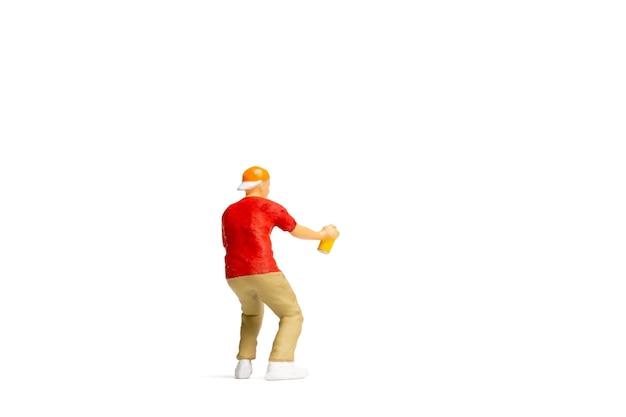 ミニチュアの人々ティーンエイジャーは白い背景とテキストのためのスペースに缶からペンキをスプレーします