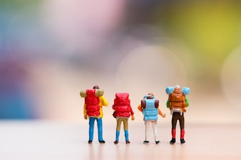Miniature people, the backpackers standing action