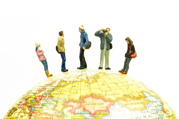 Miniature people travel around the globe close up.
