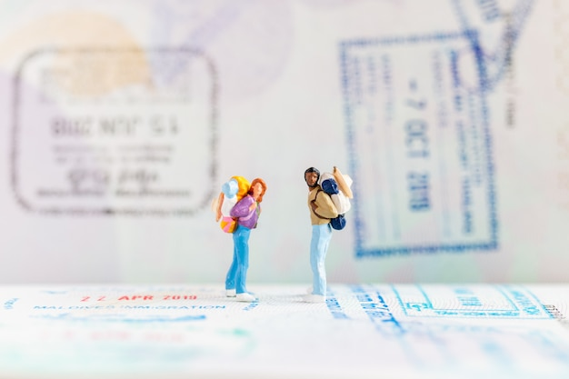 Miniature people : traveler with backpack walking on passport