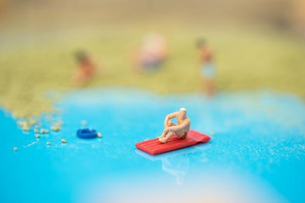 미니어처 사람들, 여름 테마로 꾸며진 모래 상자에서 편안한 여행자