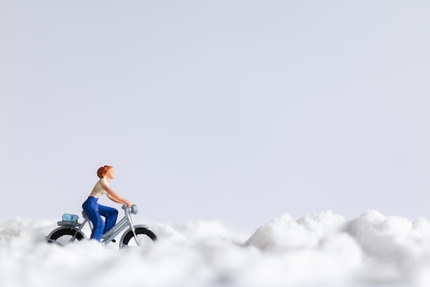Miniature people : travelers riding a bicycle on snow