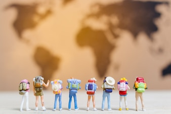 Miniature people travelers walking on world map