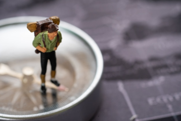 Miniature people : travelers with backpack standing on compass to tell the direction of travel.