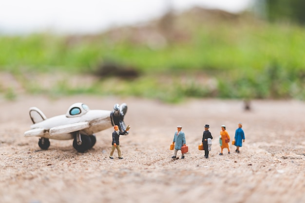 Miniature people: travellers holding carry-on luggage get on the plane