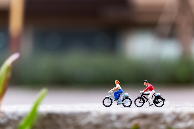 Miniature people travellers with bicycle in the park