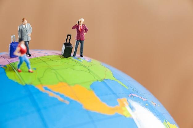 Miniature people travelling on globe