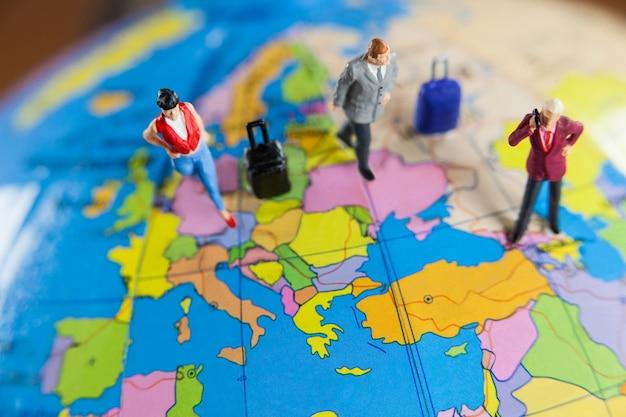 Persone in miniatura che viaggiano sul globo