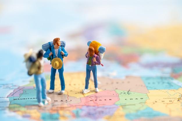 ミニチュアの人々、2人のバックパッカーは、世界地図上で驚くべき旅の旅を発見するのを楽しんでいます。