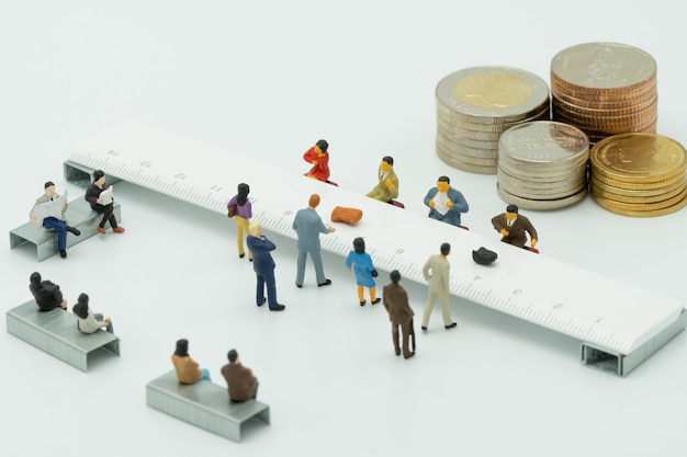 Miniature people use cash deposit. at the bank counter or financial institution.