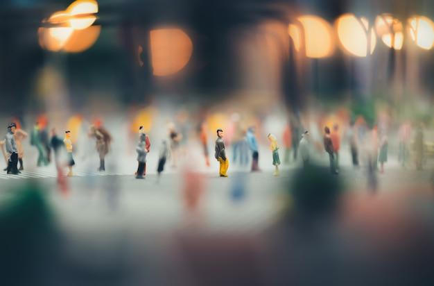 Миниатюрные люди гуляют по улицам, люди движутся по пешеходному переходу