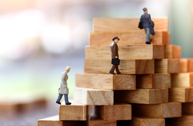Miniature people walking on step of wood block stack.