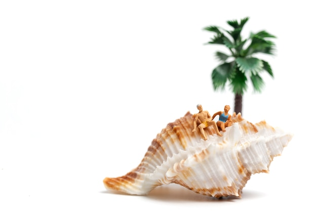 Miniature people wearing swimsuit relaxing on seashells on white background