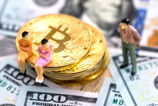 Miniature people with bitcoins and dollars