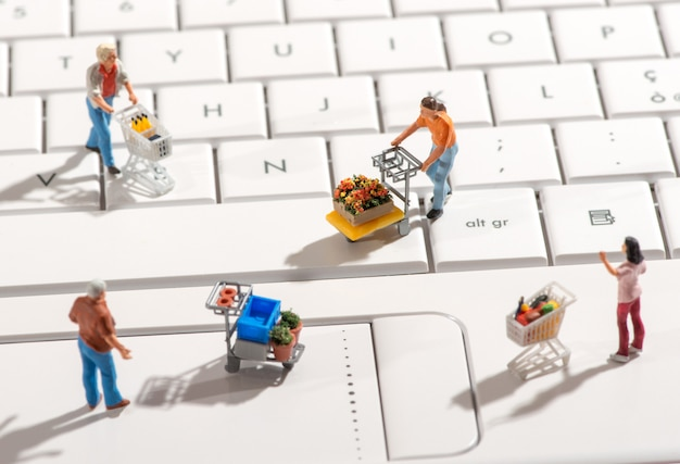 Miniature people with shopping carts on a keyboard