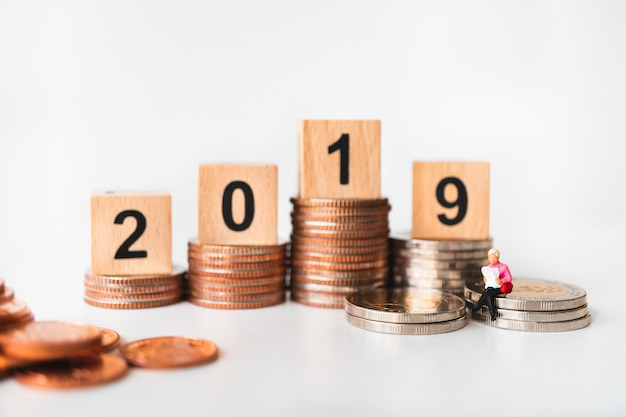 Miniature people, woman reading on stack coins with year 2019