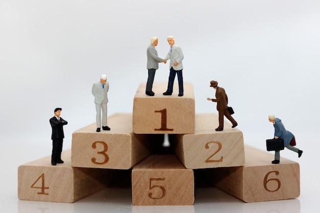 Miniature people on wooden blocks