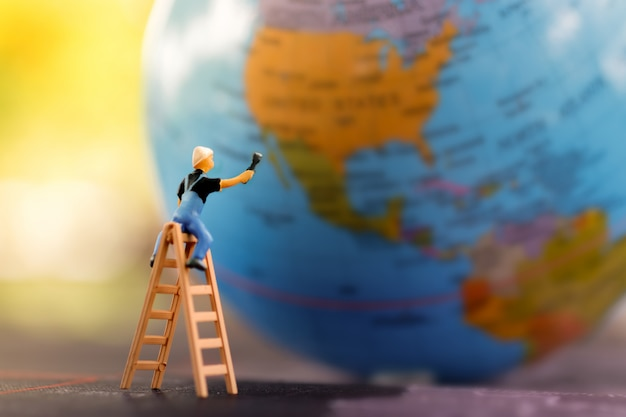 Miniature people: worker cleaning world map.