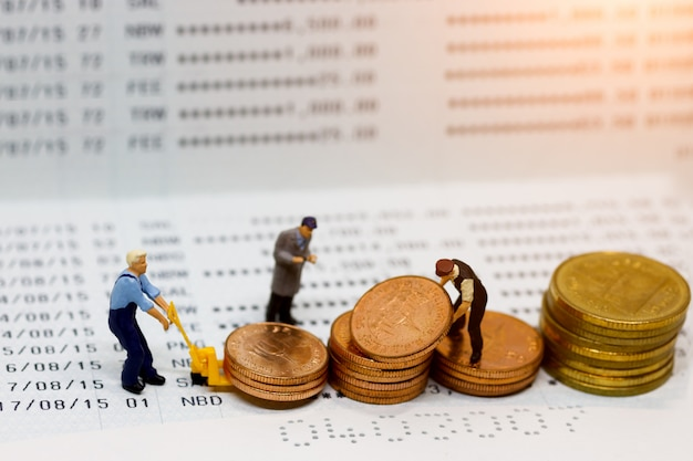 Miniature people: worker coins stack on book bank.