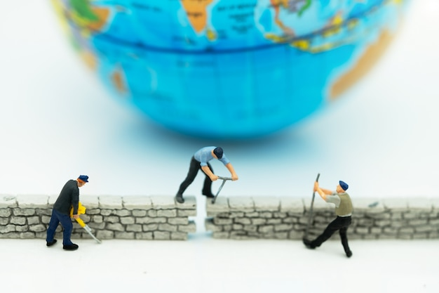 Miniature people: worker fix the wall before the world.