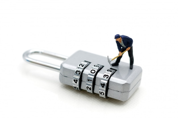 Miniature people: worker hacking in  padlock security.