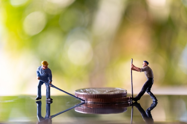 Miniature people worker holding tool on coins with green bokeh background