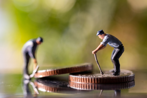 Miniature people worker holding tool on coins with green bokeh nature