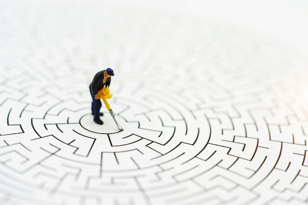Miniature people, worker man breaking down the walls in the maze