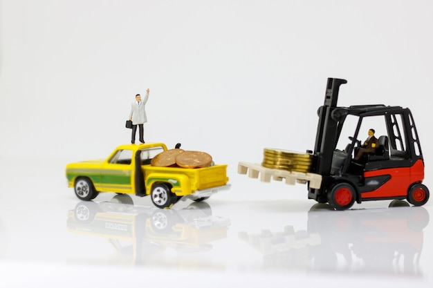 Miniature people: worker move coins stack to car.
