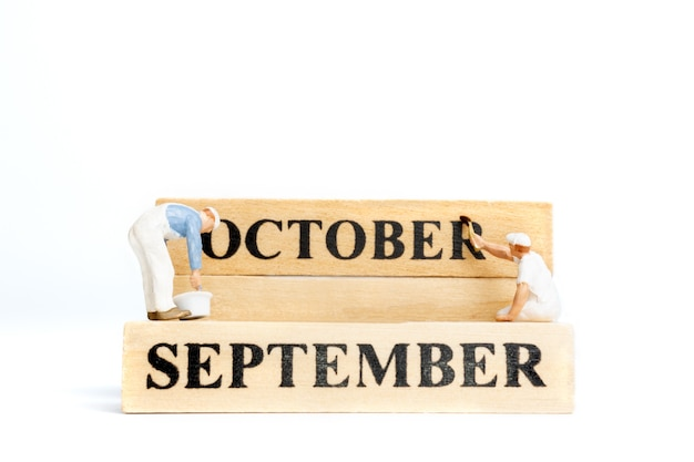 Miniature people ,worker painting october on wooden block on white background.