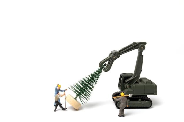 미니어처 사람들, 흰색 배경, 크리스마스 및 새해 복 많이 받으세요 개념에 크리스마스 트리를 준비하는 작업자.
