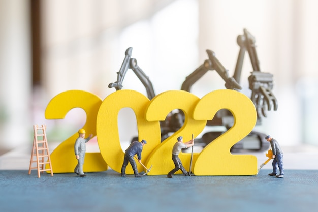 Миниатюрная команда рабочих, строящая номер 2022, концепция с новым годом