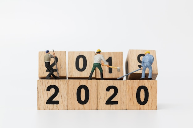 Miniature people : worker team create wooden block number 2020