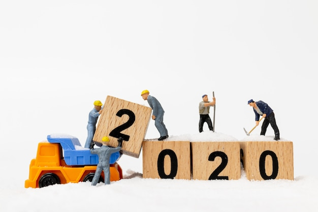 Miniature people, worker team create wooden block number 2020