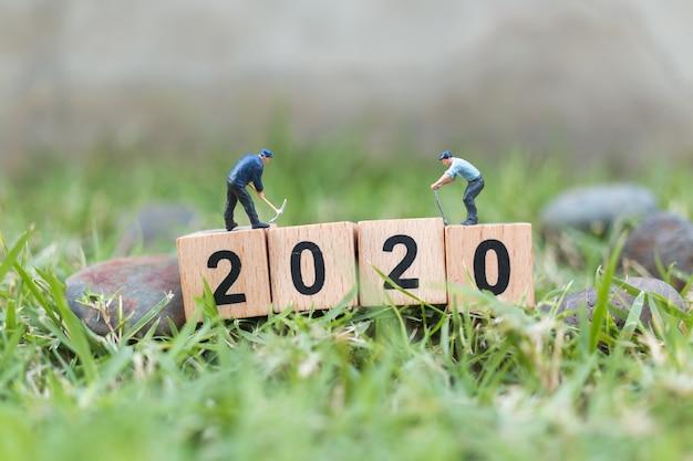Miniature people, worker team create wooden block number 2020