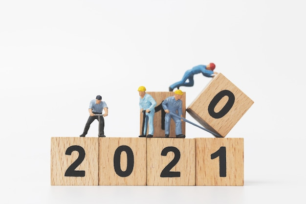 Miniature people  worker team create wooden block number 2021, happy new year concept