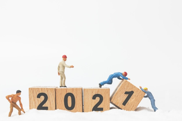Miniature people : worker team create wooden block number 2021, happy new year concept