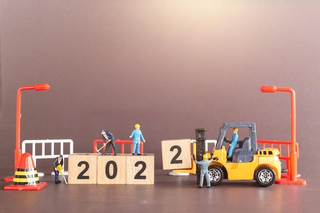 ミニチュアの人々:労働者チームは木製のブロック番号2022、新年あけましておめでとうございますのコンセプトを作成します