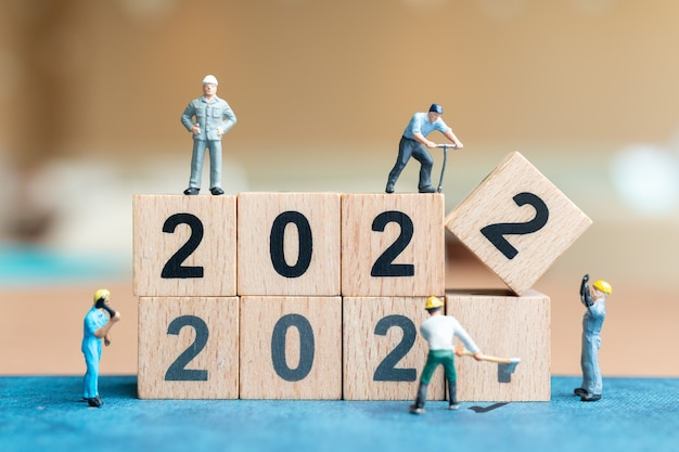 Миниатюрные люди: команда рабочих создает деревянный блок номер 2022, концепция с новым годом