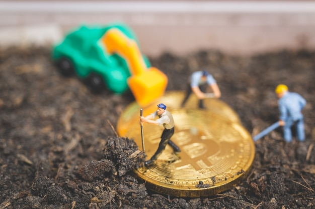 Miniature people: worker team digging ground to uncover big shiny bitcoin